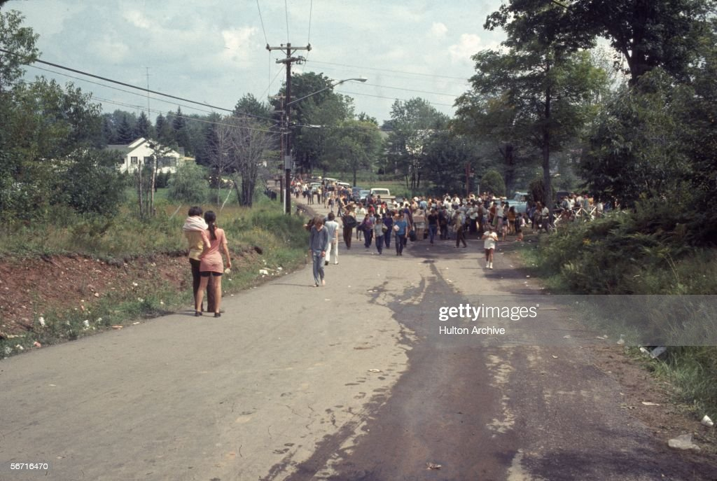 Members of the American youth subculture generally termed 'hippies' walk along a road choked with pedestrian traffic on the way to the large rock conert called Woodstock, Bethel, New York, August, 1969.