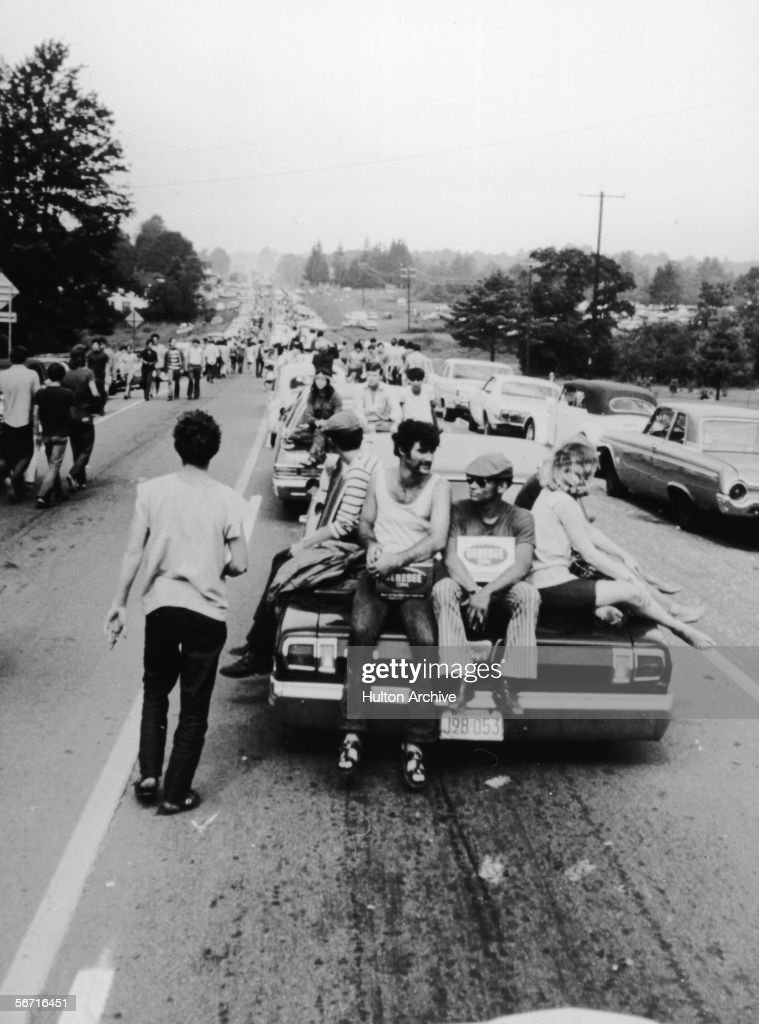 Members of the American youth subculture generally termed 'hippies' walk, or get rides on the the trunks of cars, as they move along roads choked with traffic on the way to the large rock conert called Woodstock, Bethel, New York, August, 1969.