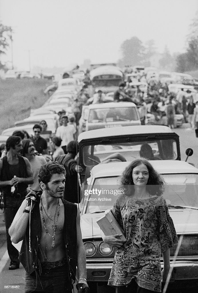 Members of the American youth subculture generally termed 'hippies' walk along roads choked with traffic on the way to the large rock conert called Woodstock, Bethel, New York, August, 1969.