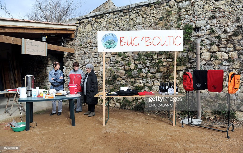 Members of the 'Amis du Pic' (Peak's friends) association propose foods and different items to visitors in their 'Bug' boutic' (Bugarach shop), on December 20, 2012 in the French southwestern village of Bugarach, near the 1,231 meter high peak of Bugarach - one of the few places on Earth some believe will be spared when the world allegedly ends according to claims regarding the ancient Mayan calendar, on December 21. French authorities have pleaded with New Age fanatics, sightseers and media crews not to converge on the tiny village. AFP PHOTO / ERIC CABANIS
