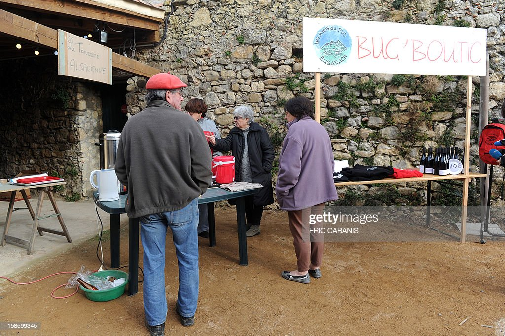 Members of the 'Amis du Pic' (Peak's friends) association propose foods and different items to visitors in their 'Bug' boutic' (Bugarach shop), on December 20, 2012 in the French southwestern village of Bugarach, near the 1,231 meter high peak of Bugarach - one of the few places on Earth some believe will be spared when the world allegedly ends according to claims regarding the ancient Mayan calendar, on December 21. French authorities have pleaded with New Age fanatics, sightseers and media crews not to converge on the tiny village.