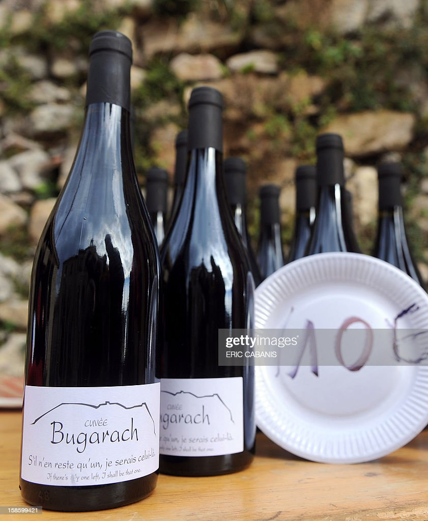 Members of the 'Amis du Pic' (Peak's friends) association propose to visitors wine for 10 euros a bottle in their 'Bug' boutic' (Bugarach shop), on December 20, 2012 in the French southwestern village of Bugarach, near the 1,231 meter high peak of Bugarach - one of the few places on Earth some believe will be spared when the world allegedly ends according to claims regarding the ancient Mayan calendar, on December 21. French authorities have pleaded with New Age fanatics, sightseers and media crews not to converge on the tiny village. The slogan on the bottle reads : 'if only one remains, I will be that one'.