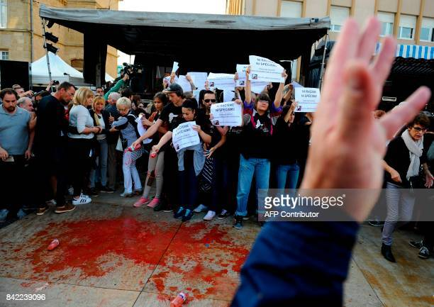 Members of the animal protection association '269 Life Liberte Animale' pour red fake blood as they demonstrate at the start of a speech by Farright...