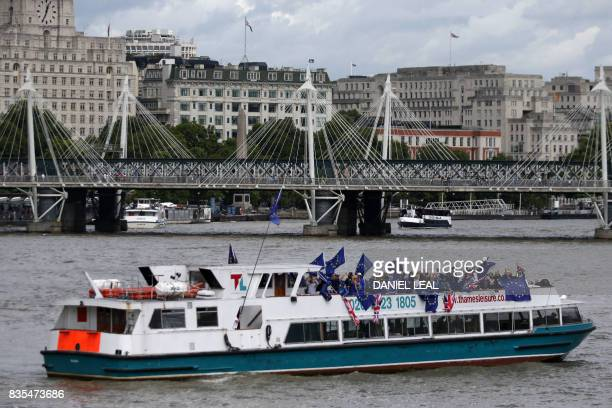 Members of the AntiBrexit campaign group The No 10 Vigil wave EU and national flags as they sail up the Thames river from the Tower Millenium Pier in...