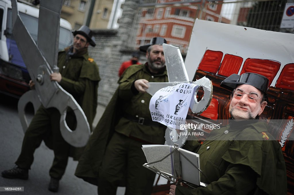 Members of the anti-military group Kakitzat wear Guardia Civil uniforms and a mask depecting Spain's Prime Minister Mariano Rajoy during a protest against government's cuts and the military budget to mark the 32nd anniversary of the attempted coup d'etat in Spain, on February 22, 2013, in the Northern Spanish Basque city of Bilbao. Banner reads 'Against unempolyment and social cuts, no to military expenses'. AFP PHOTO/ RAFA RIVAS