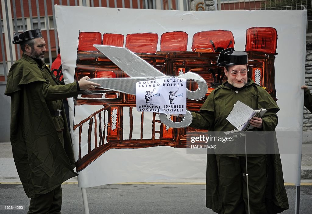 Members of the anti-military group Kakitzat wear Guardia Civil uniforms and a mask depecting Spain's Prime Minister Mariano Rajoy during a protest against government's cuts and the military budget to mark the 32nd anniversary of the attempted coup d'etat in Spain, on February 22, 2013, in the Northern Spanish Basque city of Bilbao. AFP PHOTO/ RAFA RIVAS