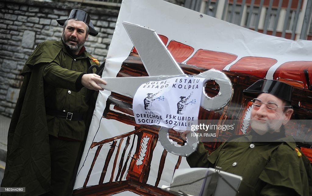 Members of the anti-military group Kakitzat wear Guardia Civil uniforms and a mask depecting Spain's Prime Minister Mariano Rajoy during a protest against government's cuts and the military budget to mark the 32nd anniversary of the attempted coup d'etat in Spain, on February 22, 2013, in the Northern Spanish Basque city of Bilbao.