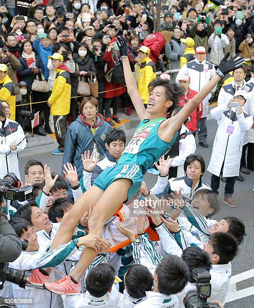Members of the Aoyama Gakuin University TokyoHakone collegiate ekiden road relay team toss anchor Yuya Ando in the air on Jan 3 in Tokyo after...