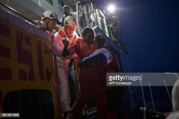 Members of the Aquarius rescue ship run by NGO SOS Mediterranee and Medecins Sans Frontieres help a child after he was rescued by the NGO Migrant...