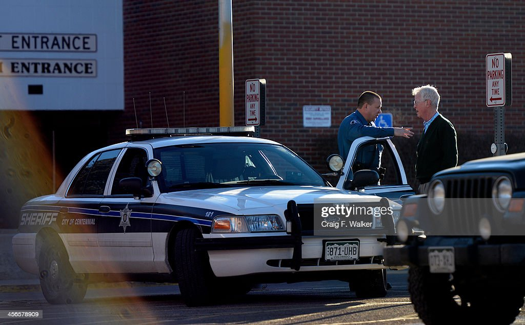 A members of the Arapahoe County Sheriff's department talks with a man in a parking lot at Arapahoe High School in Centennial, CO December 14, 2013. Karl Pierson carried a shotgun into Arapahoe High School and asked where to find a specific teacher then opened fire on Friday, wounding two fellow students before apparently killing himself, Arapahoe County Sheriff Grayson Robinson said.