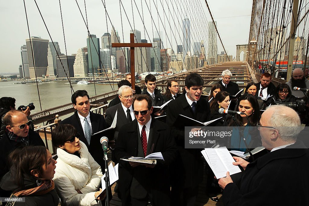 Members of the Archdiocese of New York and the Diocese of Brooklyn pause to sing during the Way of the Cross procession over the Brooklyn Bridge on April 18, 2014 in New York City. The Way of the Cross is a traditional Catholic procession recalling the suffering and death of Jesus Christ and often includes Gospel readings, choral music and readings at stations along the way. This is 19th anniversary of the procession across the iconic bridge.