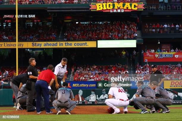 Members of the Arizona Diamondbacks and Luke Voit of the St Louis Cardinals gather around the pitcher's mound after pitcher Robbie Ray of the Arizona...
