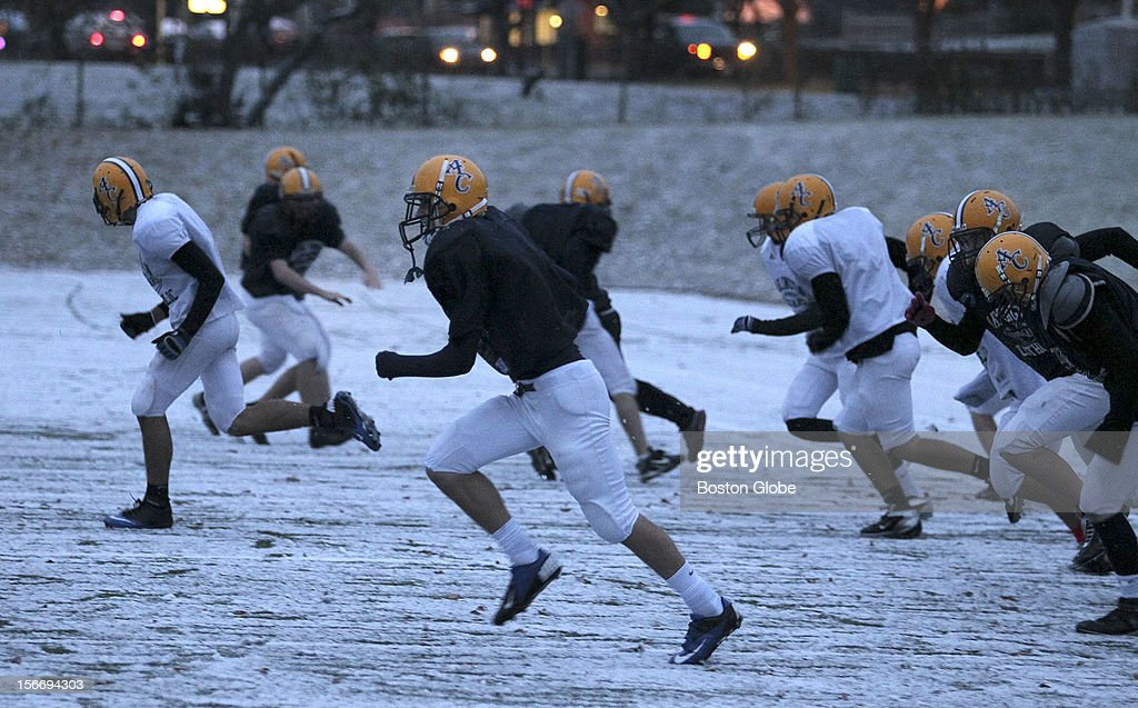 Members of the Arlington Catholic High School football team run sprints in the snow at the end of practice at their practice field on Summer Street.