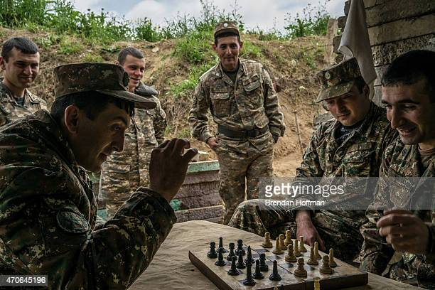 Members of the armed forces of NagornoKarabakh play checkers using a chess set at their post along the line of contact with Azerbaijani forces in the...