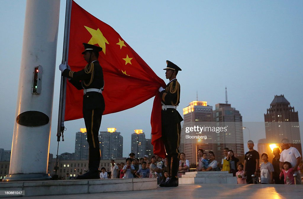 Members of the Armed Police hold China's national flag during the daily national flag-lowering ceremony at the People's Square in Dalian, China, on Friday, Sept. 13, 2013. Goldman Sachs Group Inc. this month raised its estimate for China's economic growth for the third and fourth quarters, citing improving global demand and a stronger-than-expected domestic industrial recovery. Photographer: Tomohiro Ohsumi/Bloomberg via Getty Images