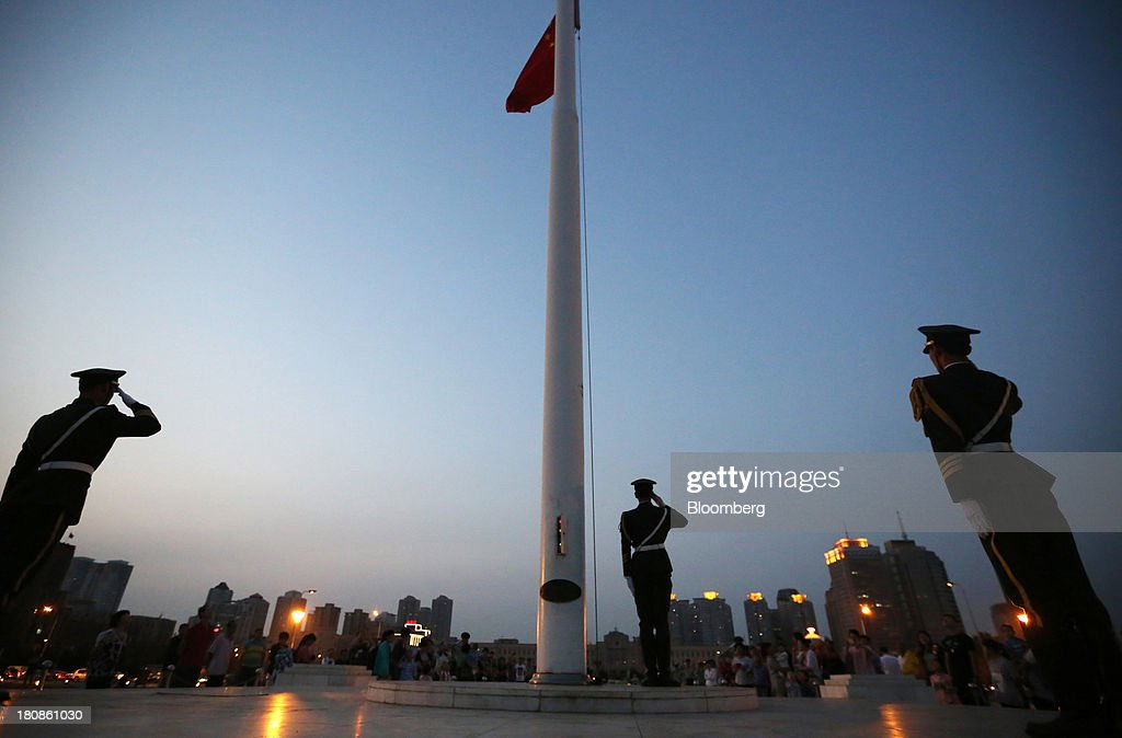 Members of the Armed Police salute during the daily national flag-lowering ceremony at the People's Square in Dalian, China, on Friday, Sept. 13, 2013. Goldman Sachs Group Inc. this month raised its estimate for China's economic growth for the third and fourth quarters, citing improving global demand and a stronger-than-expected domestic industrial recovery. Photographer: Tomohiro Ohsumi/Bloomberg via Getty Images