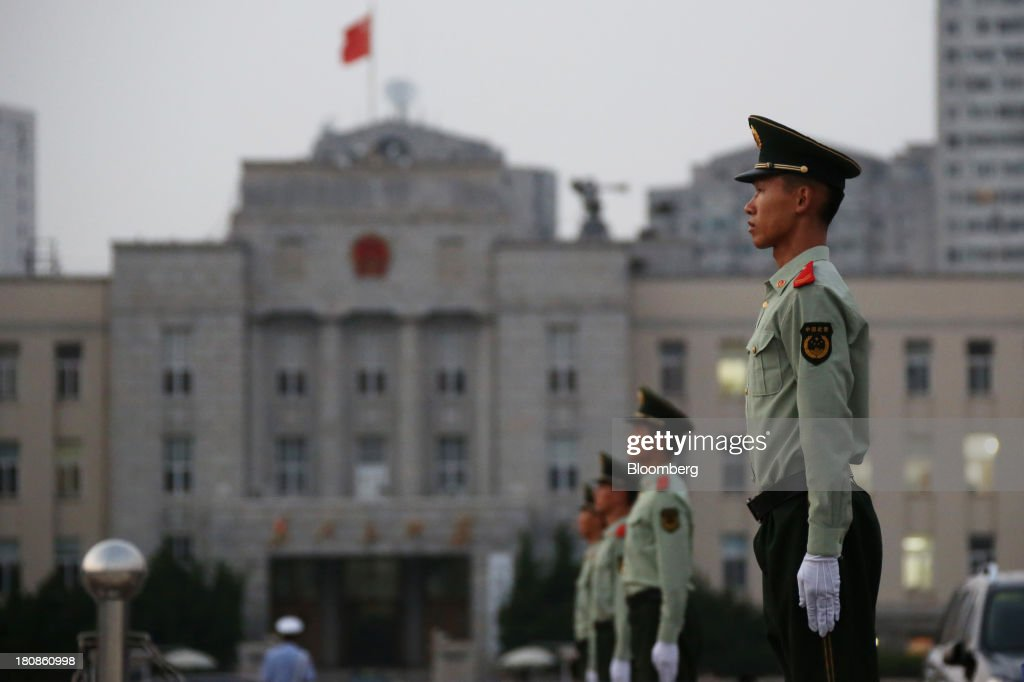 Members of the Armed Police stand during the daily national flag-lowering ceremony in front of the government office at the People's Square in Dalian, China, on Friday, Sept. 13, 2013. Goldman Sachs Group Inc. this month raised its estimate for China's economic growth for the third and fourth quarters, citing improving global demand and a stronger-than-expected domestic industrial recovery. Photographer: Tomohiro Ohsumi/Bloomberg via Getty Images