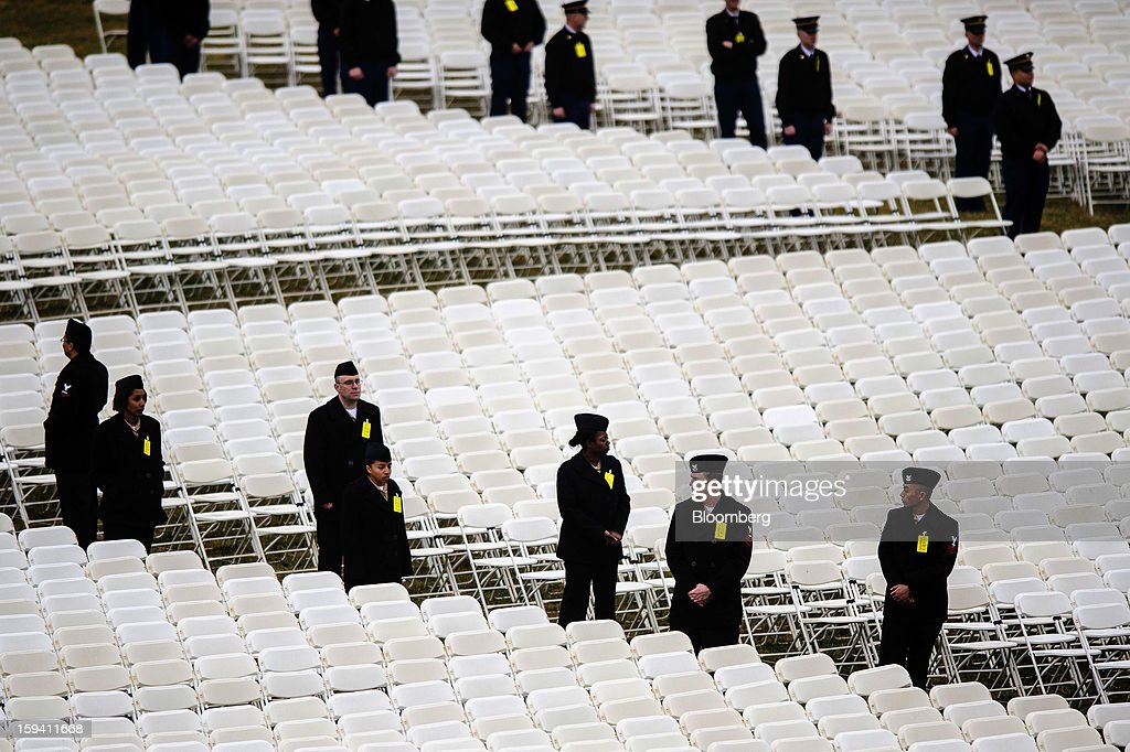 Members of the Armed Services stand next to empty seats for spectators during a dress rehearsal for the 2013 presidential inaugural ceremonies on the West Front of the U.S. Capitol in Washington, D.C., U.S., on Sunday, Jan. 13, 2013. U.S. President Barack Obama will take the oath of office for another four-year term on Monday, Jan. 21, 2013. Photographer: Pete Marovich/Bloomberg via Getty Images