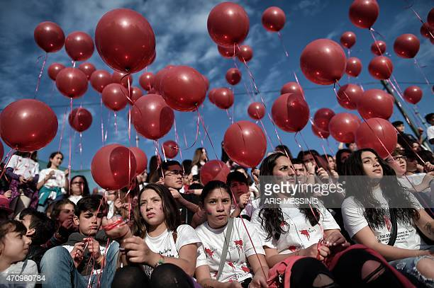 Members of the Armenian community hold balloons during a gathering to commemorate the 100th anniversary of the Armenian genocide in central Athens on...