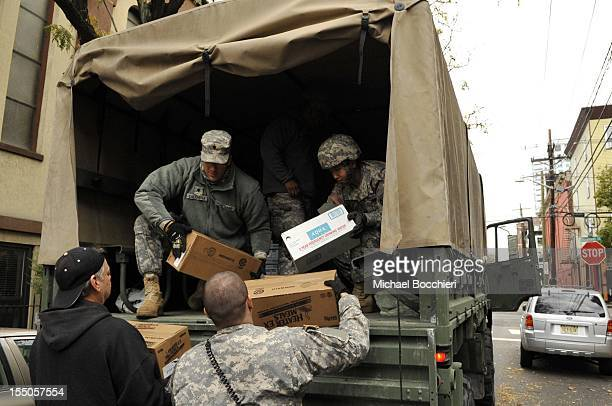 Members of the Army National Guard Unit Fox 250 from the Teaneck Armory deliver emergency drinking water to the Hoboken Homeless Shelter to aid...