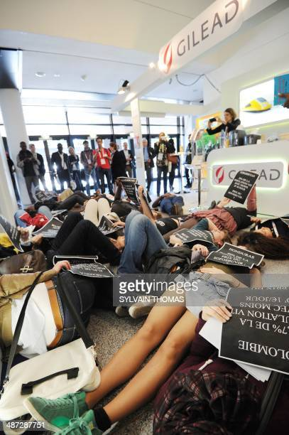 Members of the association Act Up hold signs as they lay on the floor in front of a stand of US pharmaceutical giant Gilead Sciences to denounce the...
