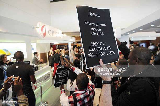 Members of the association Act Up hold signs in front of a stand of US pharmaceutical giant Gilead Sciences to denounce the high price of a new drug...