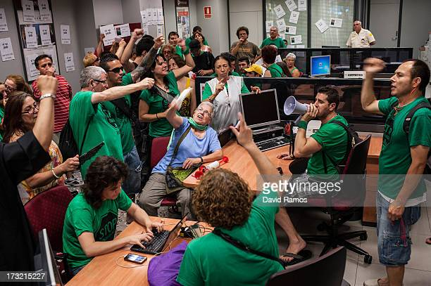 Members of the association 'Affected by the Mortgage' shout slogans as they occupy a Banco Popular bank branch on July 10 2013 in Barcelona Spain...