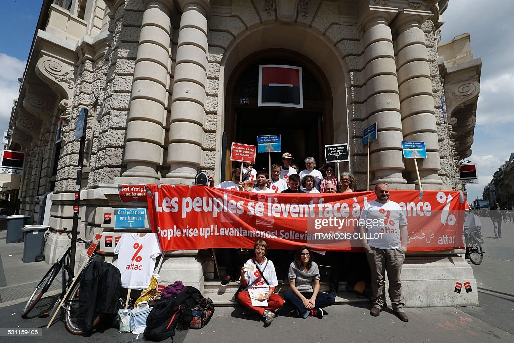 Members of the Association for the Taxation of financial Transactions and Citizen's Action (ATTAC) hold placards reading 'this is not a bank' as they demonstrate outside the French bank Societe Generale in Paris on May 25, 2016. / AFP / FRANCOIS