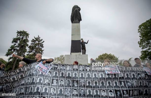Members of the Association of Families of Kidnapped and Murdered in Kosovo cover with a black cloth an inscription on the monument of Gratitude to...