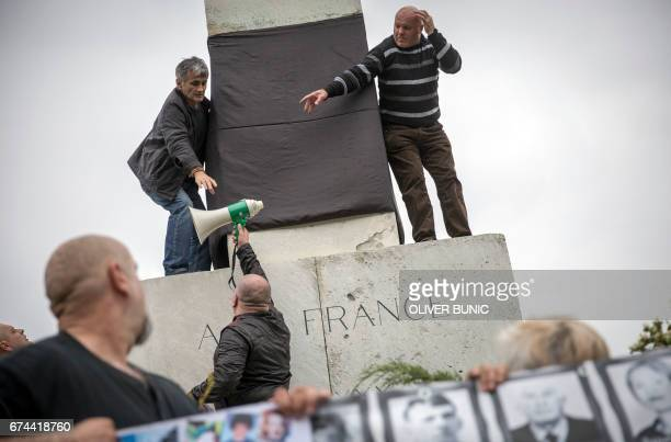 Members of the Association of Families of Kidnapped and Murdered in Kosovo take part in a rally in front of the monument of Gratitude to France which...