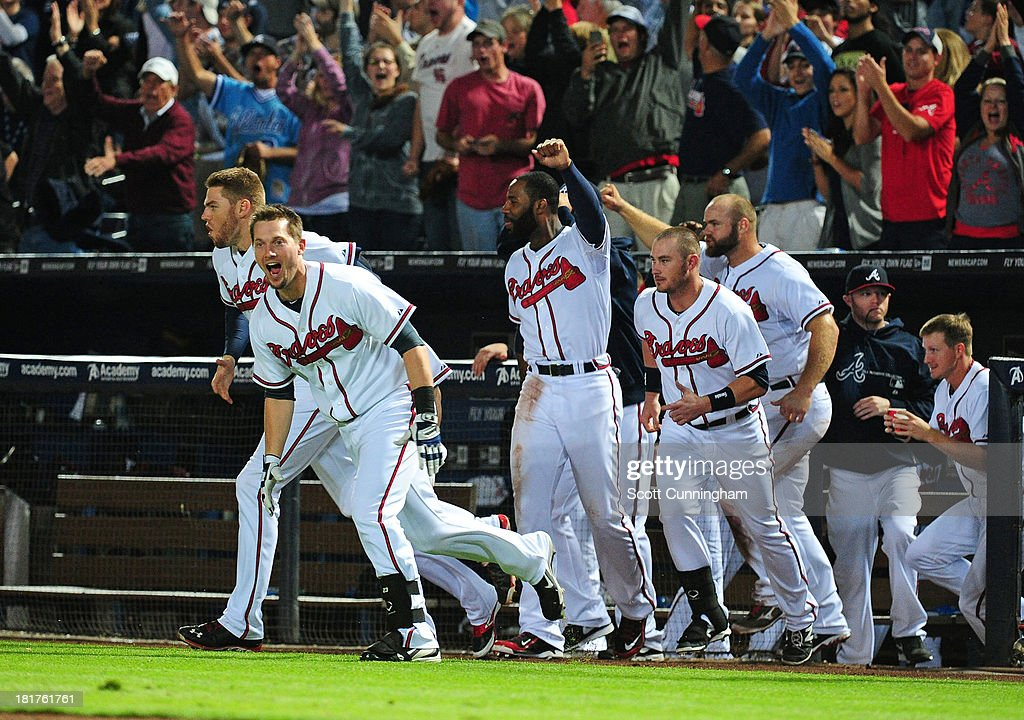Members of the Atlanta Braves stream out of the dugout after a game-winning single in the 9th inning by Andrelton Simmons #19 (not pictured) against the Milwaukee Brewers at Turner Field on September 24, 2013 in Atlanta, Georgia.