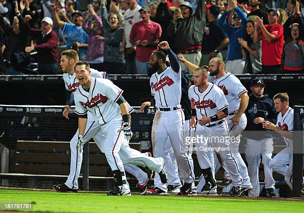 Members of the Atlanta Braves stream out of the dugout after a gamewinning single in the 9th inning by Andrelton Simmons against the Milwaukee...
