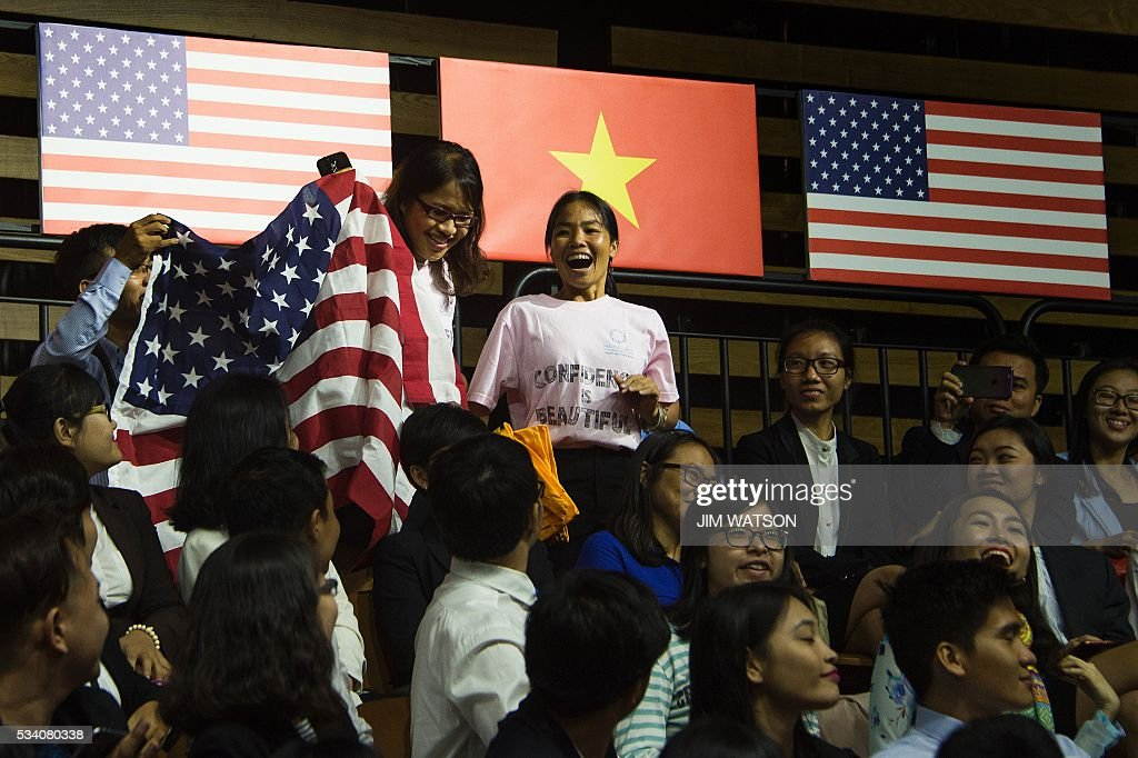 Members of the audience hold up a flag and pose a question to US President Barack Obama as he speaks at the Young Southeast Asian Leaders Initiative town hall event in Ho Chi Minh City on May 25, 2016. Obama urged communist Vietnam on May 24 to abandon authoritarianism, saying basic human rights would not jeopardise its stability, after Hanoi barred several dissidents from meeting the US leader. / AFP / JIM