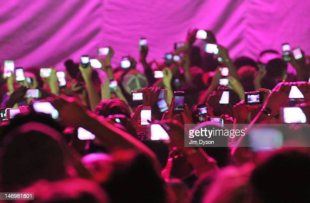 Members of the audience hold up cameras and mobile telephones as American rapper and RB singer Nicki Minaj takes to the stage stage during her 'Pink...