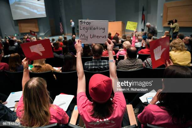 Members of the audience hold up signs as US Representative Mike Coffman takes questions during his town hall meeting in the main auditorium of the...