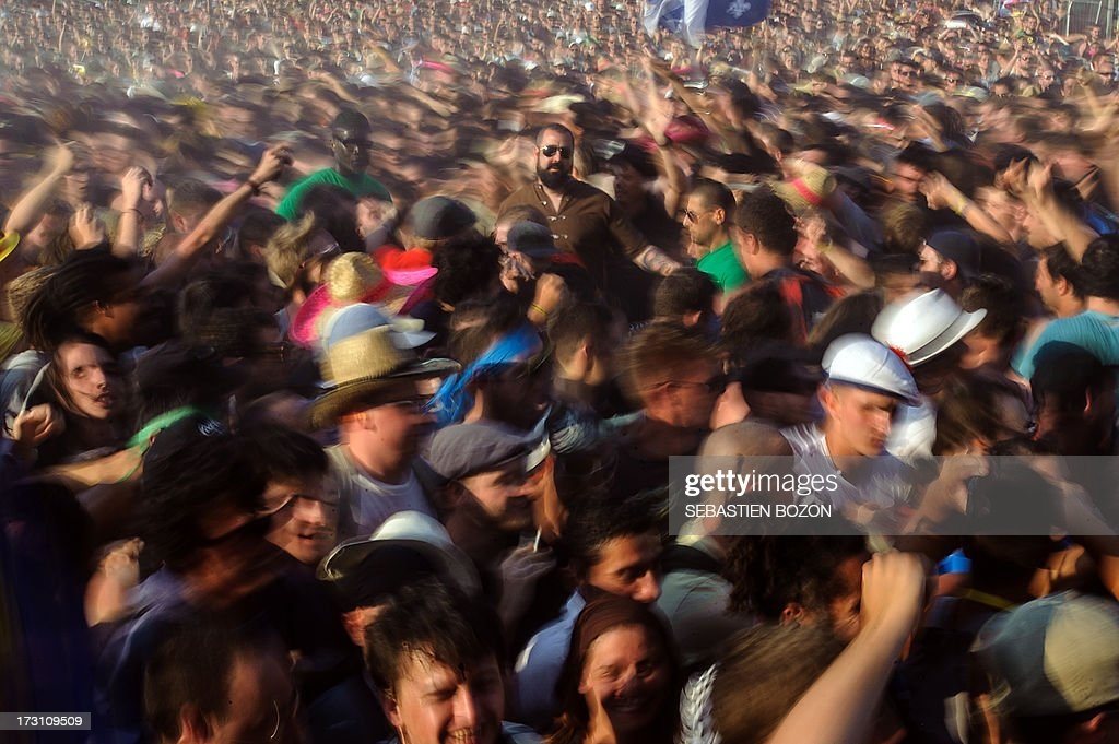 Members of the audience turns around French band Mass Hysteria (C) performs in the middle of the crowd during a concert on July 7, 2013 at the Eurockeennes music festival in the eastern France city of Belfort.