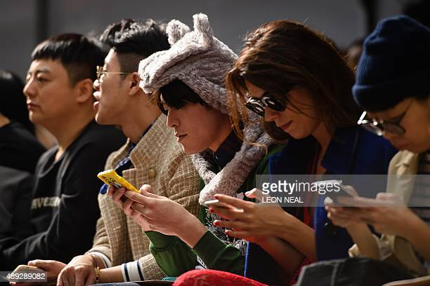 Members of the audience use their mobile phones ahead of a show by Georgian designer David Koma during the Spring / Summer 2016 London Fashion Week...