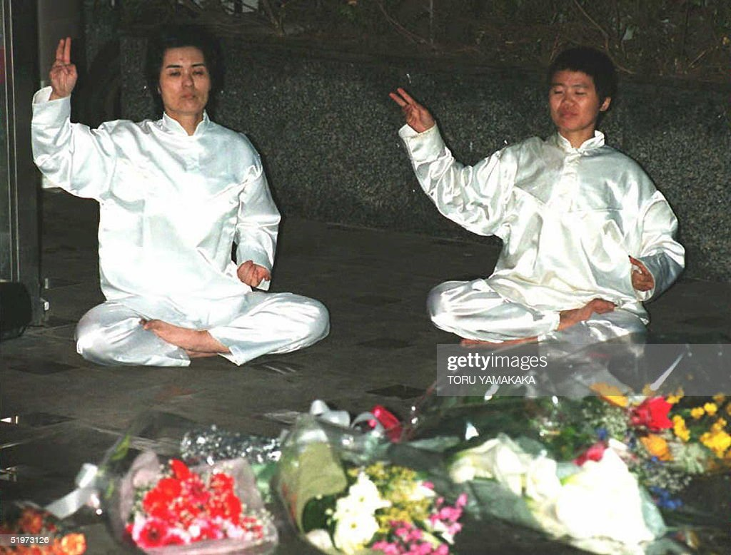 Members of the Aum Shinrikyo (Supreme Truth) sit on the ground to perform a rite 24 April to pay tribute to the late 'Science and Technology minister' of the sect, Hideo Murai, 36, who was stabbed to death late 23 April in front of Aum's Tokyo headquarters.