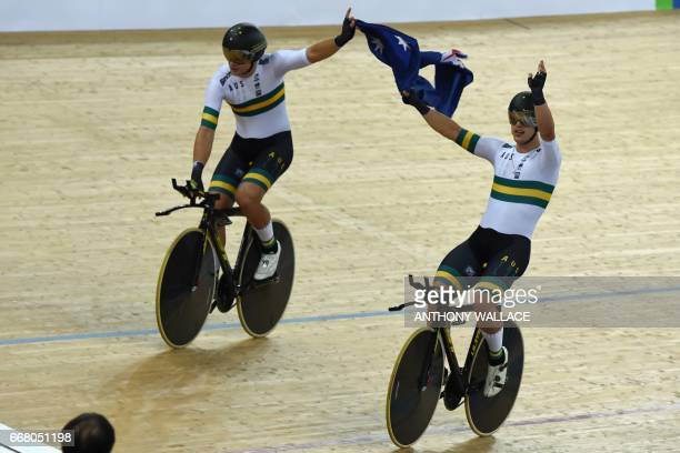 Members of the Australia team hold their national flag after they won the final of the men's team pursuit event at the Hong Kong Velodrome during the...
