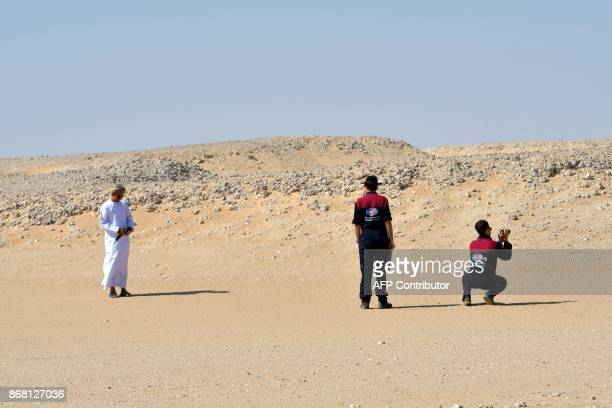 TOPSHOT Members of the Austrian Space Forum inspect a site in Oman's Dhofar desert near the southern Marmul outpost on October 29 in preparation for...