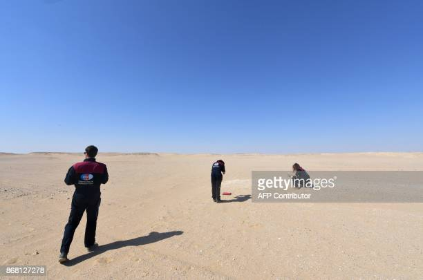 Members of the Austrian Space Forum inspect a site in Oman's Dhofar desert near the southern Marmul outpost on October 29 in preparation for a...