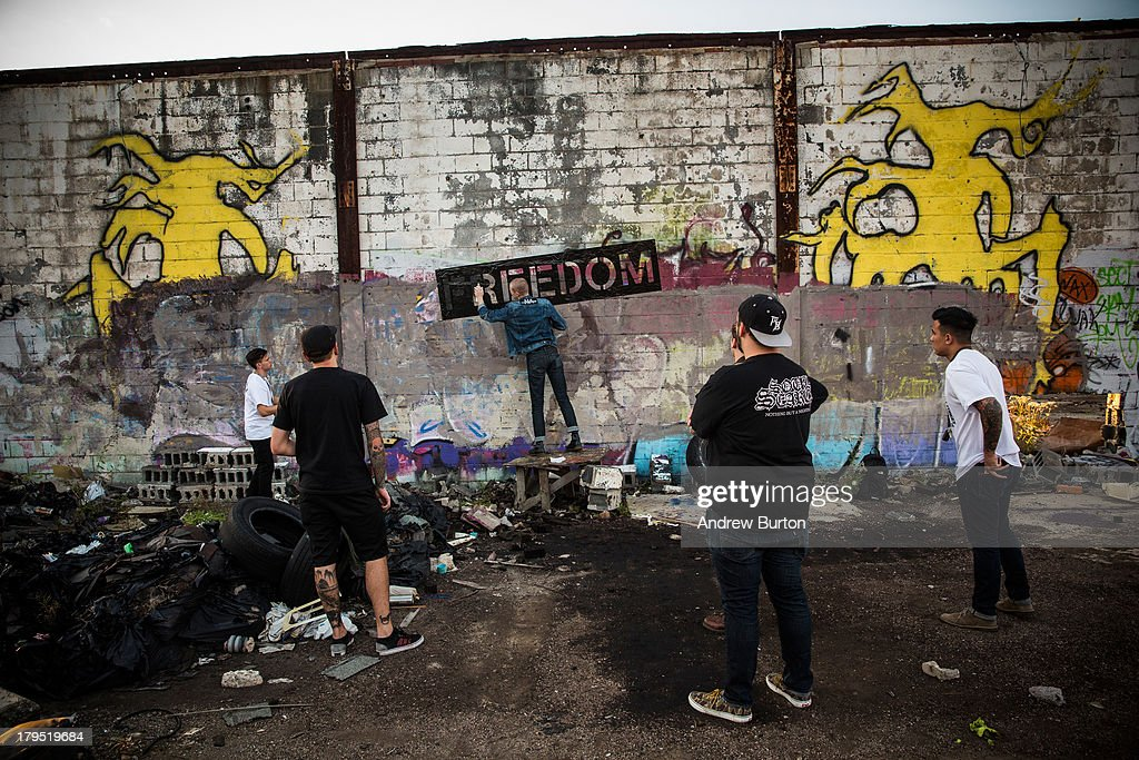 Members of the band 'Freedom' spray paint their name on a wall at the abandoned Packard Automotive Plant on September 4, 2013 in Detroit, Michigan. The Packard Plant was a 3.5 million square foot car manufacturing plant built completed in 1911. Major operations ceased in 1958, though the plant was used in a limited capacity until the 1990s, with outer buildings used through the mid 2000s. Since then the buildings have fallen into disrepair - they are now used mostly for graffitti artists and scavengers. Detroit has an astonishing 78,000 abandoned buildings across its 142 square miles. Last month the city declared bankruptcy, the largest municipality to ever do so in the United States.