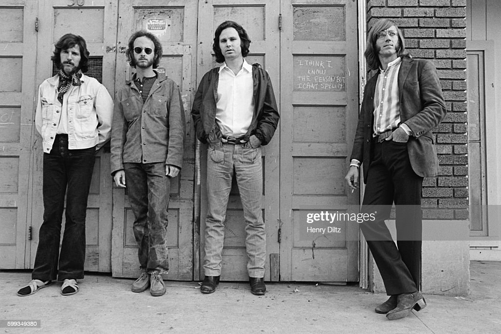 Members of the band The Doors stand in front of a door on which is written