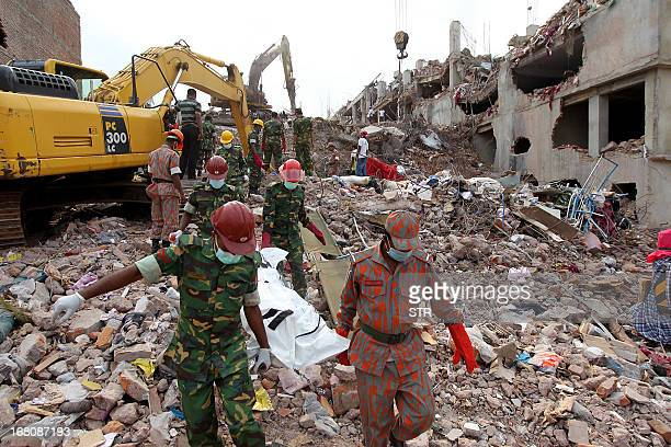 Members of the Bangladeshi Army and fire fighters carry the body of a garment worker as heavy equipment is brought in to remove debris following an...