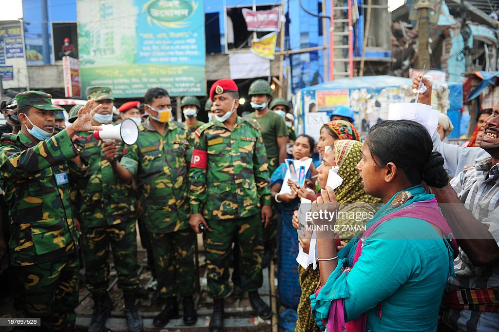 Members of the Bangladeshi Army speak to family members of workers, believed to be trapped in the rubble of an eight-storey building that collapsed, on the situation in Savar, on the outskirts of Dhaka, on April 28, 2013. Four people were hauled out alive overnight more than 90 hours after the disaster, but the last feeble cries for help, still audible from inside the mountain of rubble early in the day, appeared to have ended. Rescue teams at the site of a collapsed factory block in Bangladesh where 363 people have died called in heavy-lifting equipment as hopes of finding more survivors faded. AFP PHOTO/ Munir uz ZAMAN