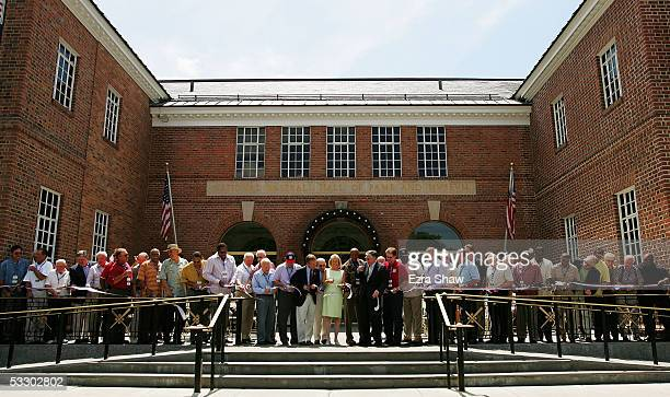 38 members of the Baseball Hall of Fame along with board members and state senators cut a ribbon during a rededication ceremony at the National...