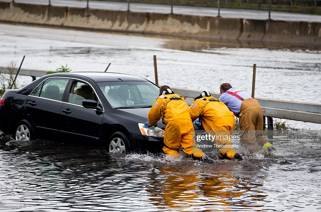 Members of the Bayshore Fire Department push a car stuck in the water at Sunrise Highway under the 5th Ave overpass following heavy rains and flash flooding August 13, 2014 in Bayshore, New York. The south shore of Long Island along with the tri-state region saw record setting rain that caused roads to flood entrapping some motorists.