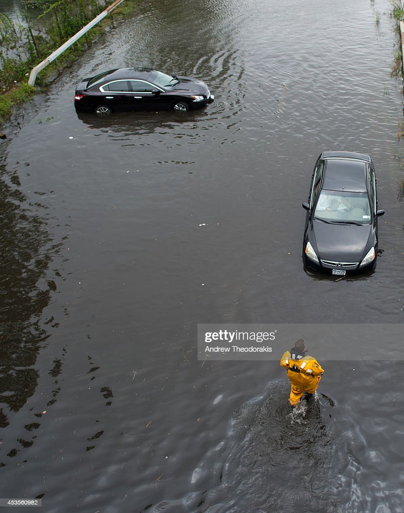 Members of the Bayshore Fire Department survey flood damage at Sunrise Highway following heavy rains and flash flooding August 13, 2014 in Bayshore, New York. The south shore of Long Island along with the tri-state region saw record setting rain that caused roads to flood entrapping some motorists.