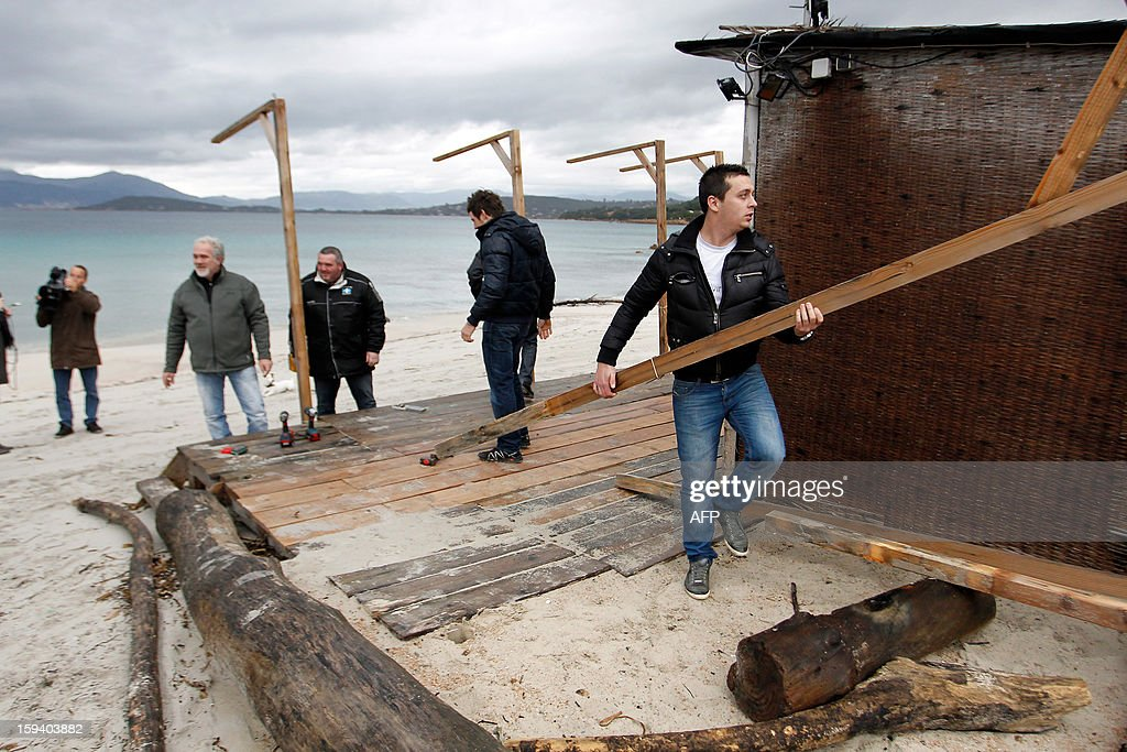 Members of the beach huts protection group symbolically demolish on January 13, 2013 parts of the 'Beach Hut of the Silver Beach' restaurant in front of the press in Porticcio. The South Corsica prefecture has ordered beach hut owners to demolish the parts that are located on the public property before January 15. If not respected the prefecture will conduct the demolition itself. AFP PHOTO / PASCAL POCHARD-CASABIANCA