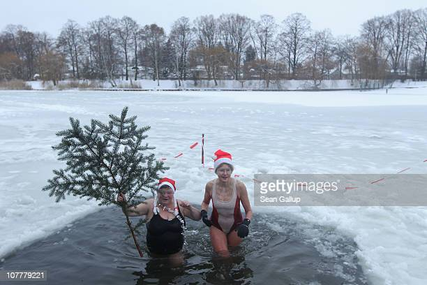 Members of the Berlin Seals swimming club take a dip in icy Orankesee lake during their traditional Christmas Day ice swim on December 25 2010 in...